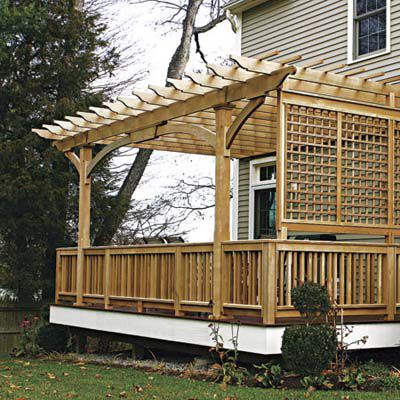 Wooden screen on the side of a backyard patio and pergola.
