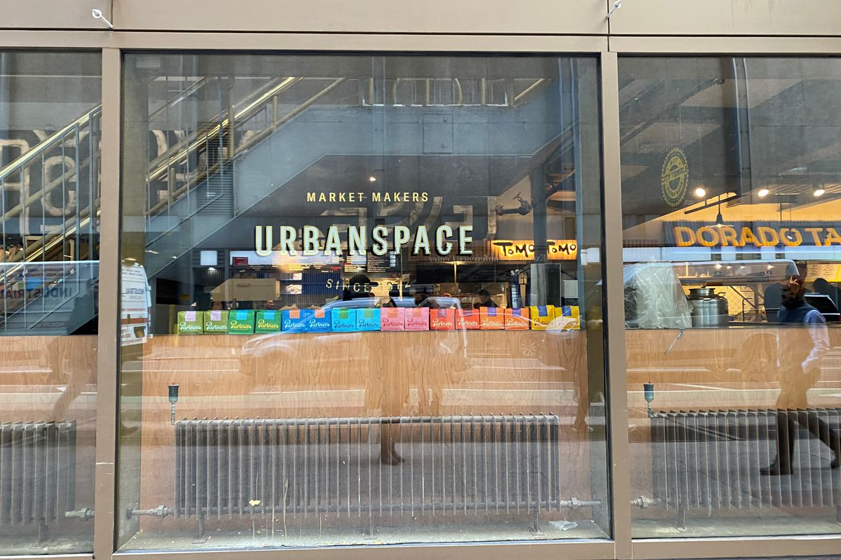 The glass exterior of the urbanspace food hall with the name of the space emblazoned in gold letters on the front
