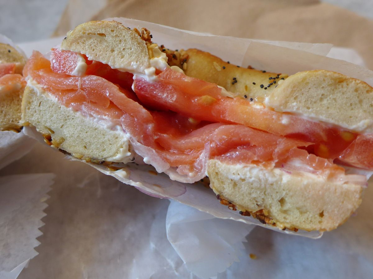 A bagel split in half with bright orange lox and white cream cheese showing.