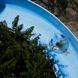 A boy slides down a slide at Seven Peaks Waterpark in Salt Lake City on Sunday, June 18, 2017. Pools and waterparks may be the place to be this week as temperatures are expected to approach 100 degrees along the Wasatch Front.