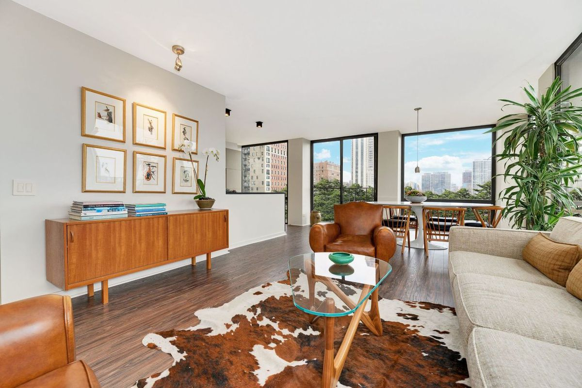A living room with large windows, hardwood floors, and white walls. There is a brown couch with a cowhide rug, a credenza, framed photos on the wall, and a potted plant.