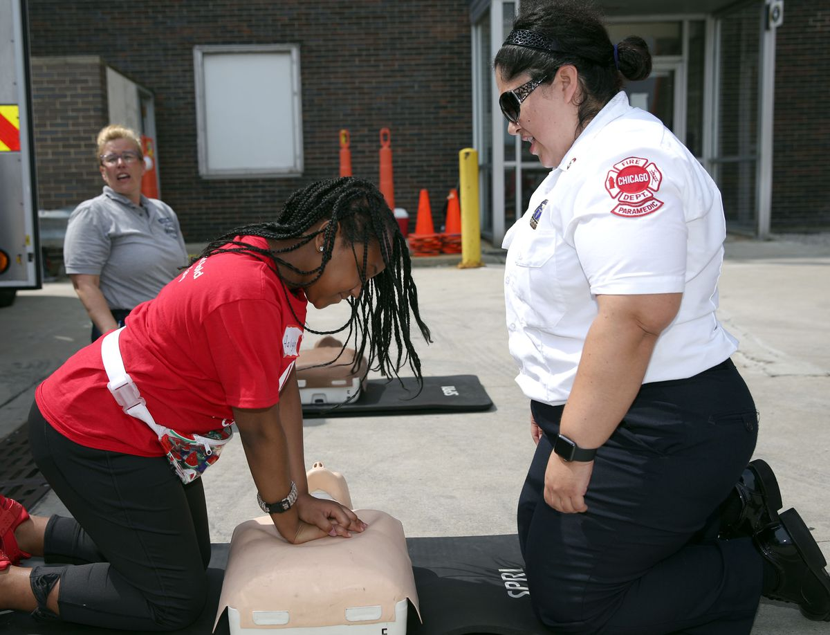 """Aaliyan performs CPR under the direction of Nor Duran during the """"Girls Inc. Firefighter for a Day"""" program in Chicago Friday June 28, 2019."""