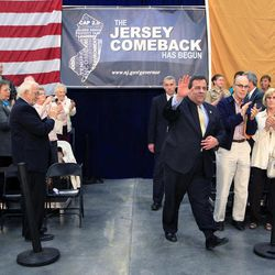 In this March 29, 2012 photo, New Jersey Gov. Chris Christie waves as he arrives for a town hall meeting in Manchester, N.J. Part stump speech, part quiz show, part comedy hour, Chris Christie's town halls are probably not what Norman Rockwell envisioned in his famous 1943 painting of an assembly where people come to air their grievances and an elected official listens patiently. Yet the time-old tradition of the town hall has become the hallmark of Christie's administration and helped make him a rising Republican star.
