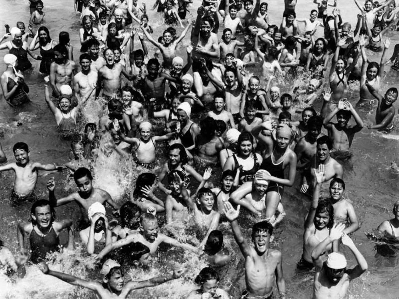 A black and white image of dozens of children splashing, smiling, and throwing their arms in the air as they pose for an overhead photograph.