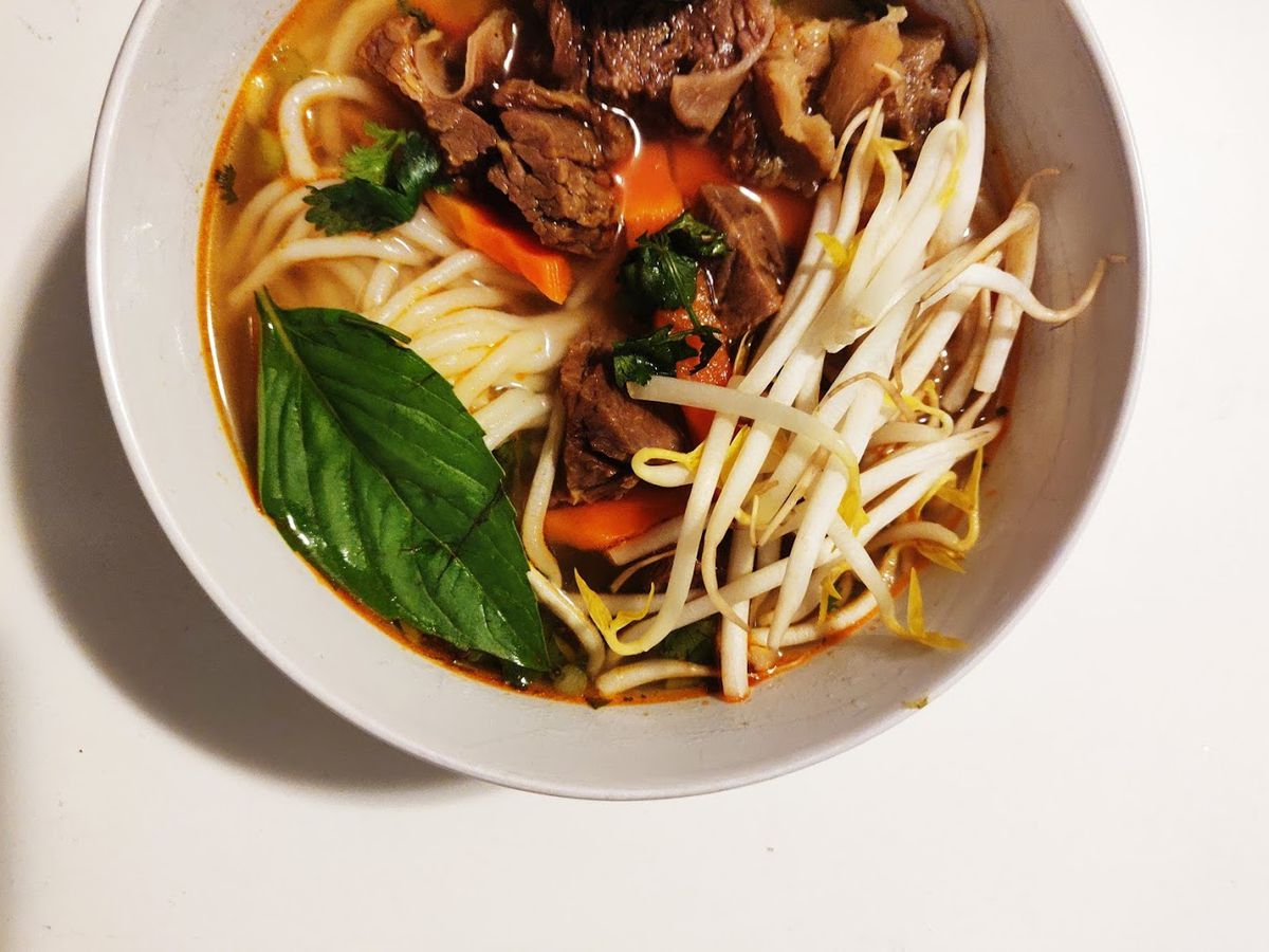 A bowl of bo kho, which is a Vietnamese beef and noodle soup, as seen from overhead