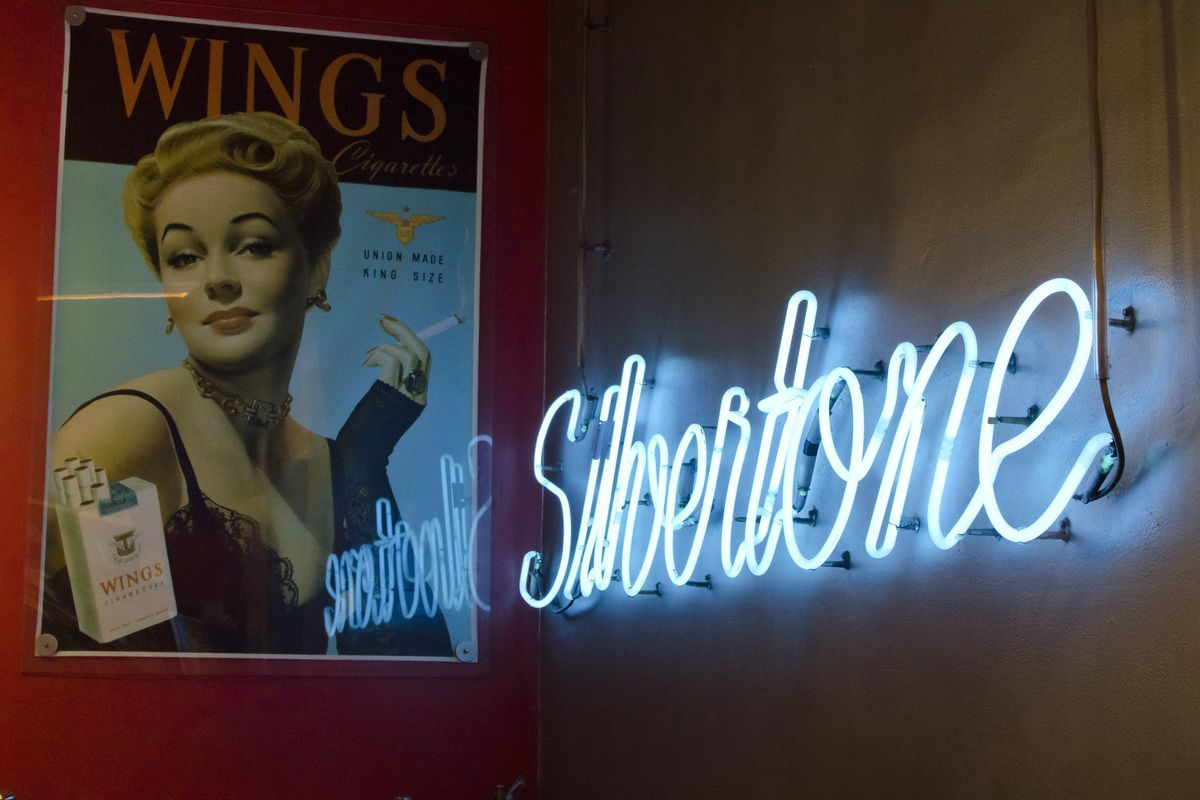 A vintage cigarette poster hangs on a red wall, across a corner from a blue neon sign that reads Silvertone.