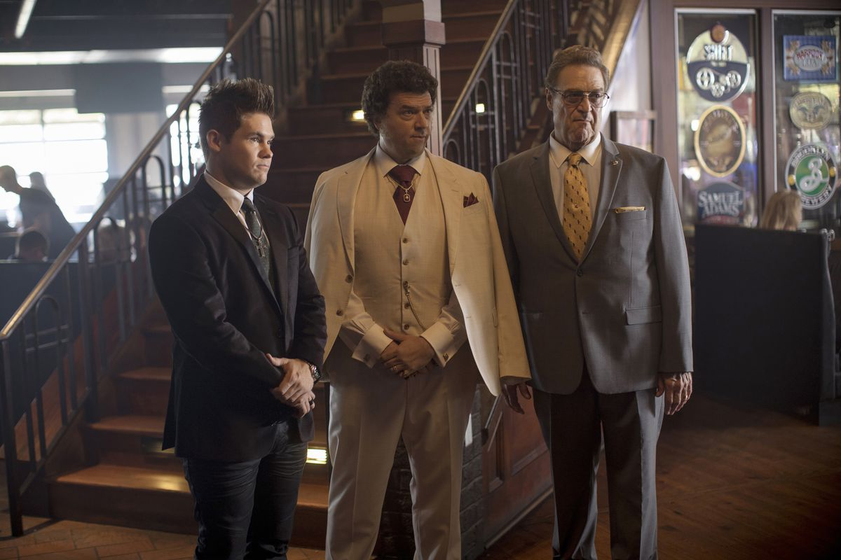 """Three men in the cast of """"The Righteous Gemstones"""" wearing suits and standing beside an interior staircase."""