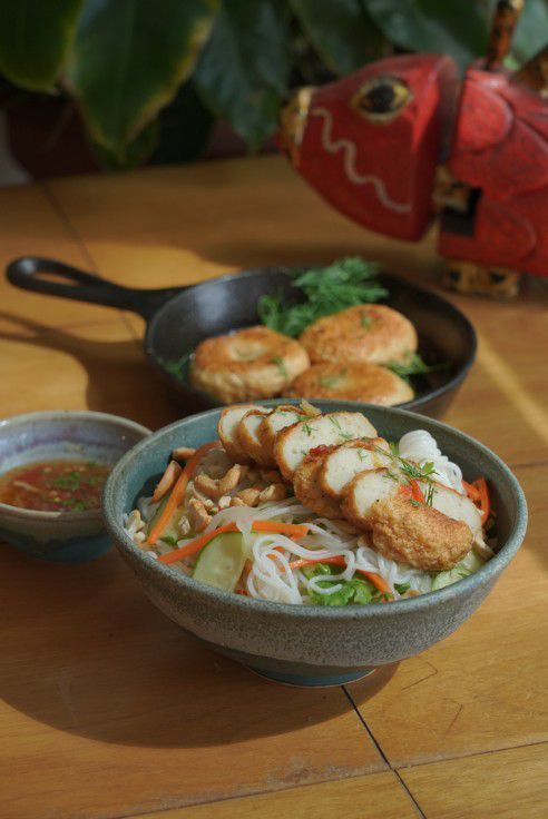 A speckled gray bowl contains sliced fish cakes atop vermicelli noodles and various garnishes. A cast iron skillet with fish cakes sits in the background.