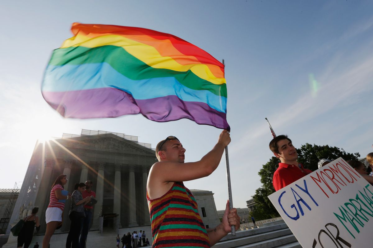 An activist waves an LGBT flag in front of the Supreme Court.