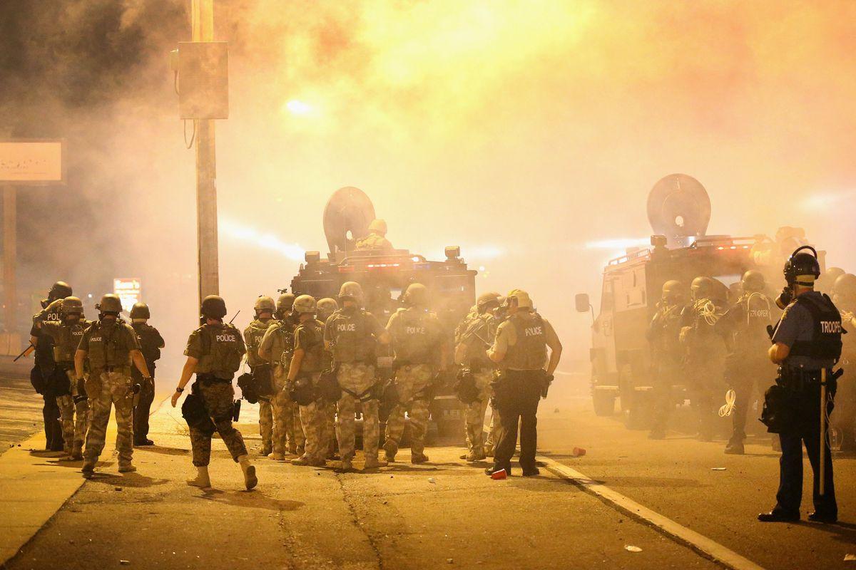 FERGUSON, MO - AUGUST 17: Police advance through a cloud of tear gas Scott  Olson