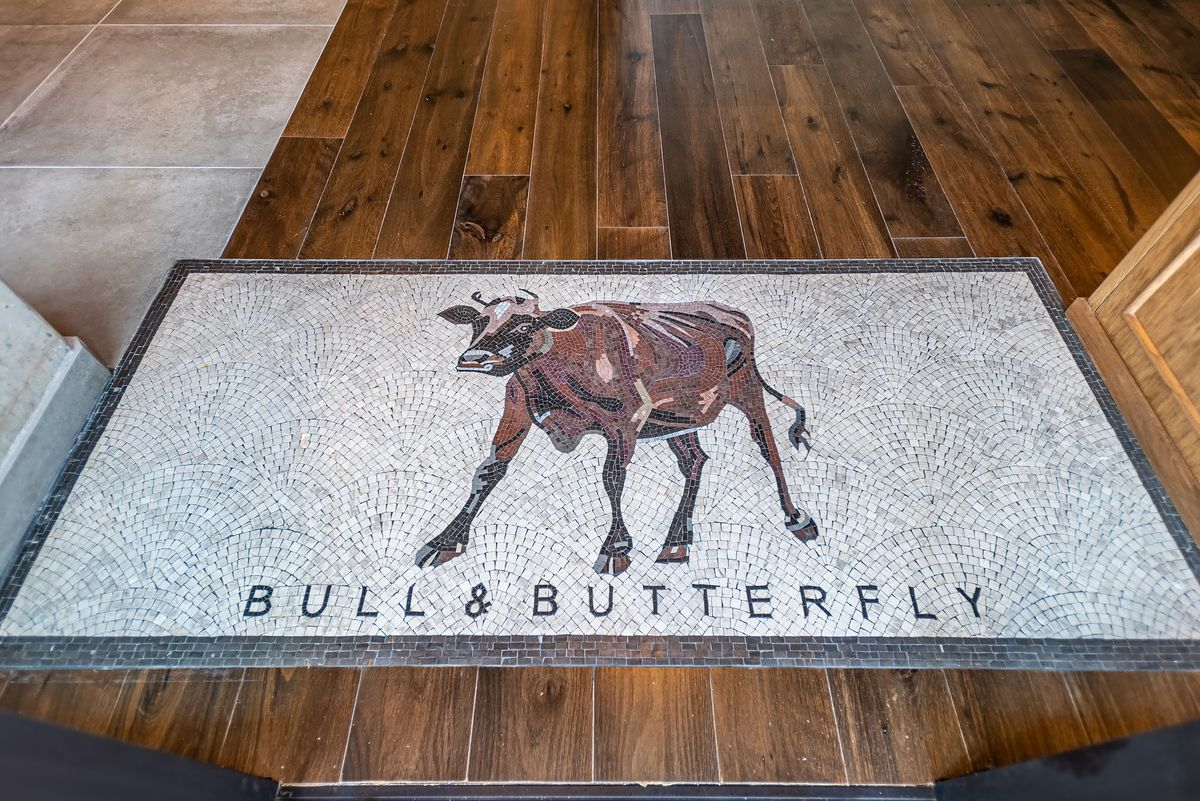 Inlaid tile at a front door of a new steakhouse reads Bull & Butterfly.