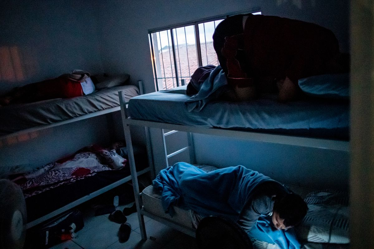 Elder Tanner McKee prays while his companion, Elder Pedro Cabral, shuts off the alarm on their shared cellphone as they awake at their home in Paranaguá, Brazil, on Sunday, June 2, 2019. Elders McKee and Cabral awoke early, at 6:30 a.m., to walk a family to church while Elder Felipe Araujo and Elder Jeffrey Eidem, left, continue to sleep.