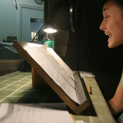 """Narrator Jennifer Ikeda, right, reads from Anne Dayton and May Vanderbilt's """"Emily Ever After,"""" under the direction of Jeff Baron, left in shadows, during a recording session for an audiobook at Recorded Books Productions in New York, on Aug. 29, 2005."""