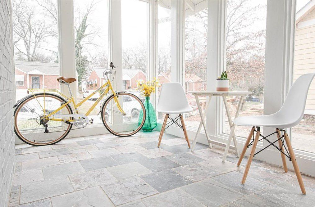 A white sunroom with two chairs and a bike and many windows.