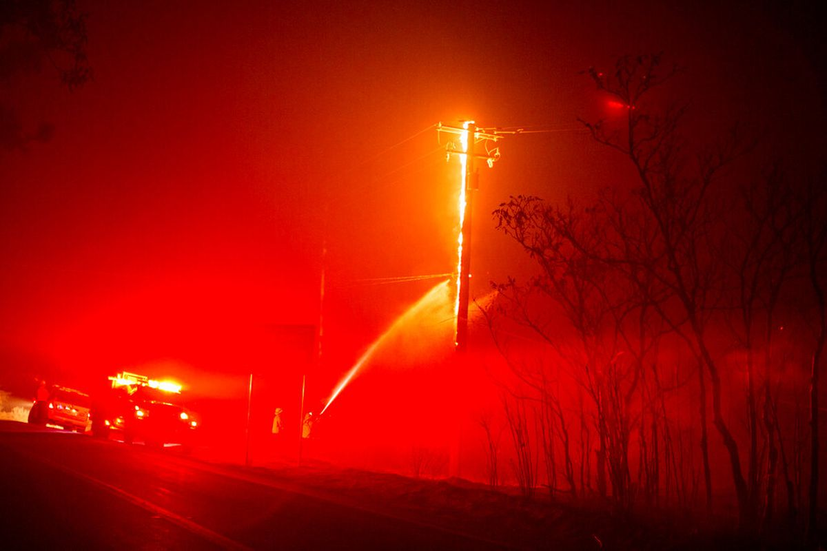 A firefighter sprays on a power pole burning by the Lake Hughes fire in Angeles National Forest.