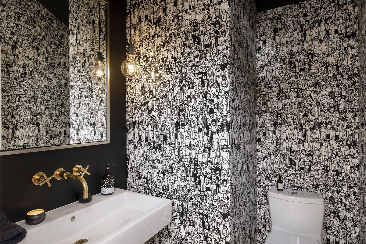 A wallpaper with black-and-white figures decorates a powder room.