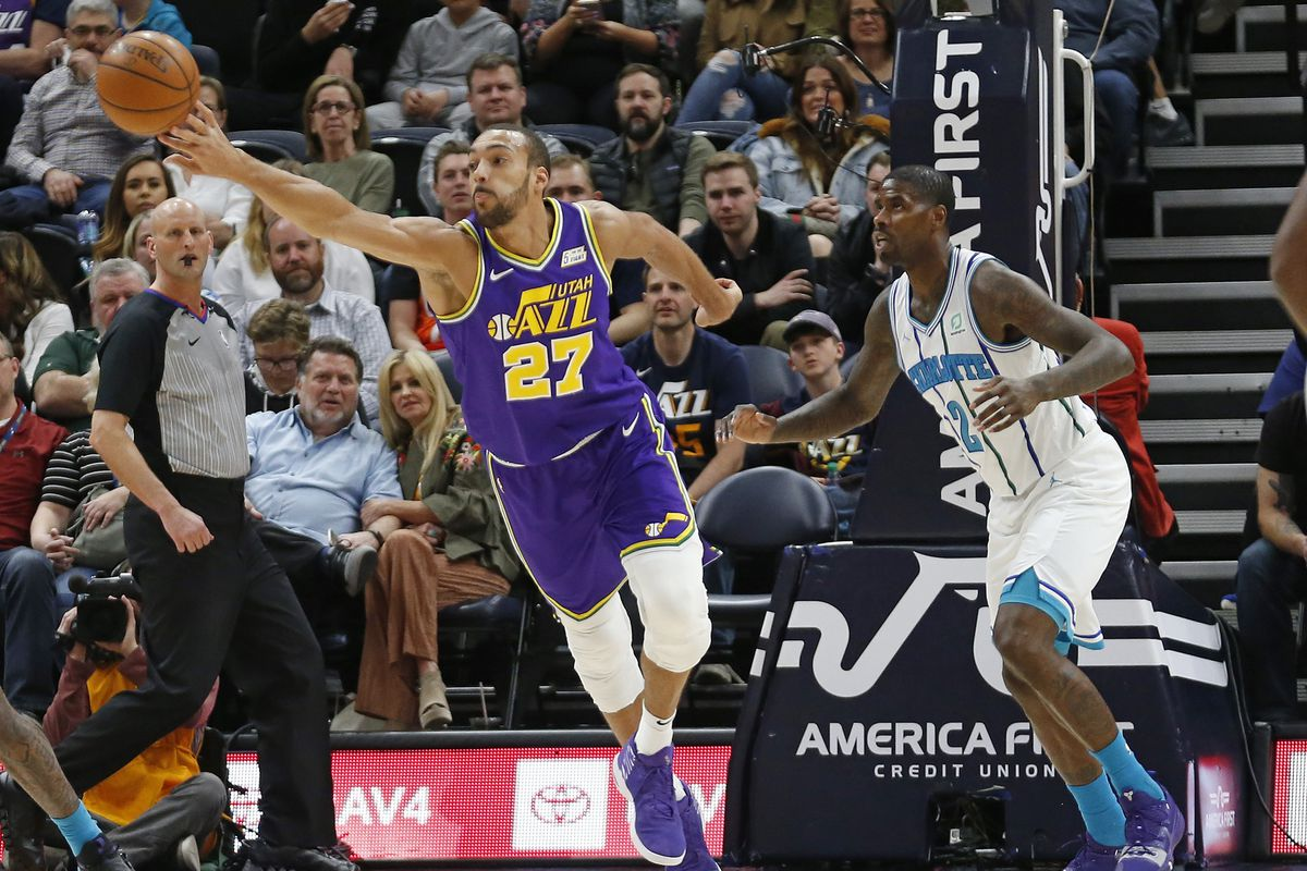Utah Jazz center Rudy Gobert (27) reaches for the ball as Charlotte Hornets forward Marvin Williams (2) looks on during the first half of an NBA basketball game Monday, April 1, 2019, in Salt Lake City. (AP Photo/Rick Bowmer)