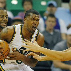Utah's Dominic McGuire is defended by Warrior's Andre Iguodala and teammate Klay Thompspon as they Utah Jazz and the Golden State Warriors play Tuesday, Oct. 8, 2013 in preseason action at Energy Solutions arena in Salt Lake City.
