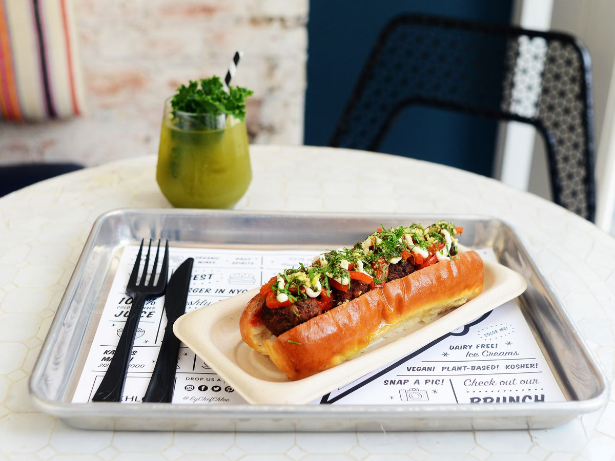 Meatballs sit in a glossy hot dog-style roll on a metal tray that's covered with a white placemat with a lot of text on it in a modern font. There's plasticware on the tray, which sits on a white table.