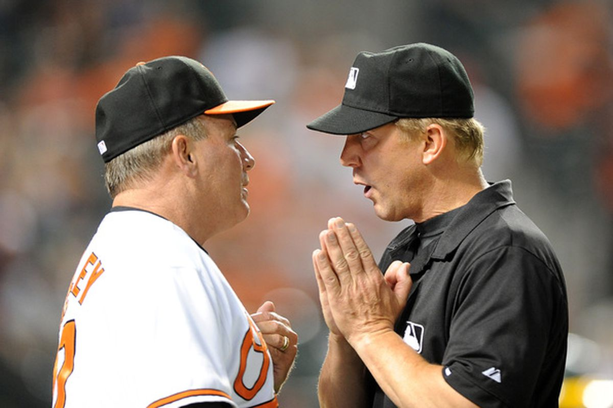 Umpire Jeff Kellogg explains to Dave Trembley why he's so bad at managing. (Photo by Greg Fiume/Getty Images)
