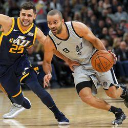 San Antonio Spurs' Tony Parker (9) drives around Utah Jazz' Raul Neto during the first half of an NBA basketball game, Saturday, Feb. 3, 2018, in San Antonio. (AP Photo/Darren Abate)