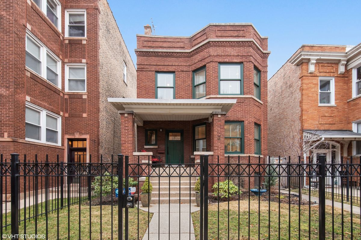 A two-story brick home with a front yard and metal fence.