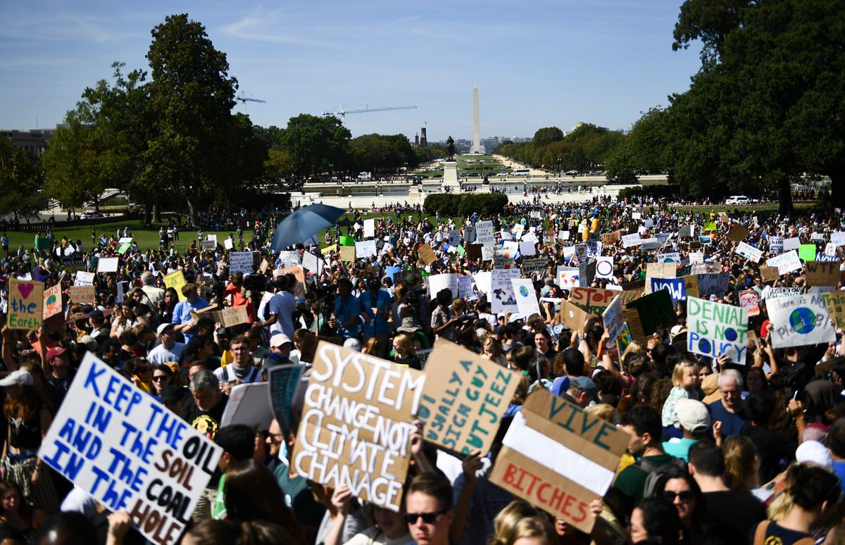 "At the Global Climate Strike on the mall in Washington, DC, signs read, ""Keep the oil in the soil and the coal in the hole,"" and, ""System change not climate change."""