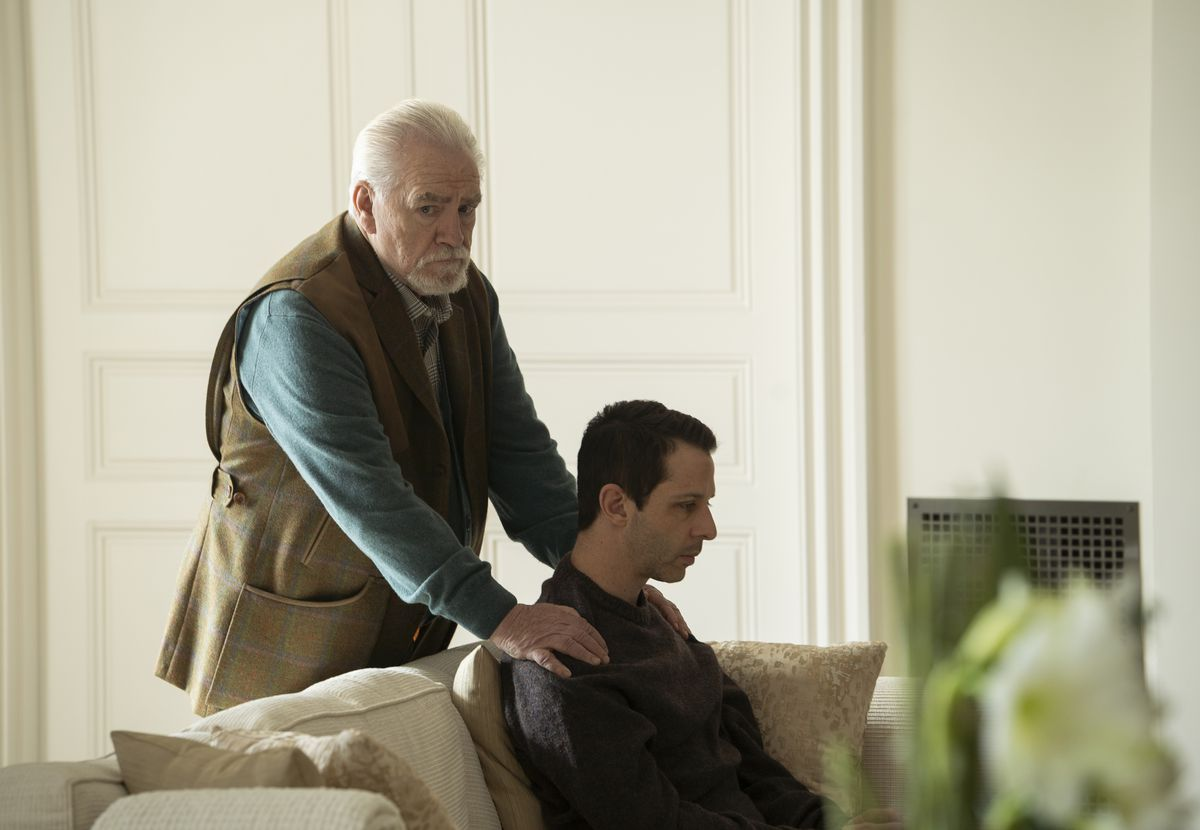 Logan (Brian Cox) places his hands on a seated Kendall's (Jeremy Strong) shoulders in a photo from Succession.