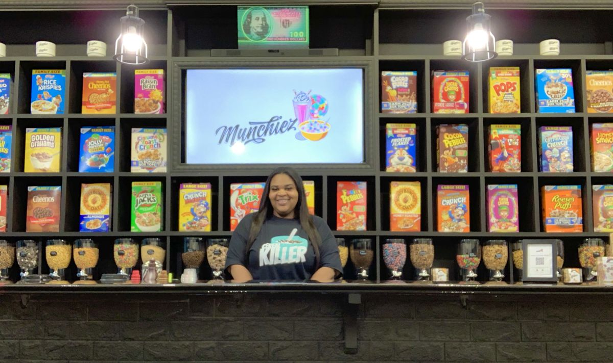 A Black woman stands in front a display of cereal boxes.