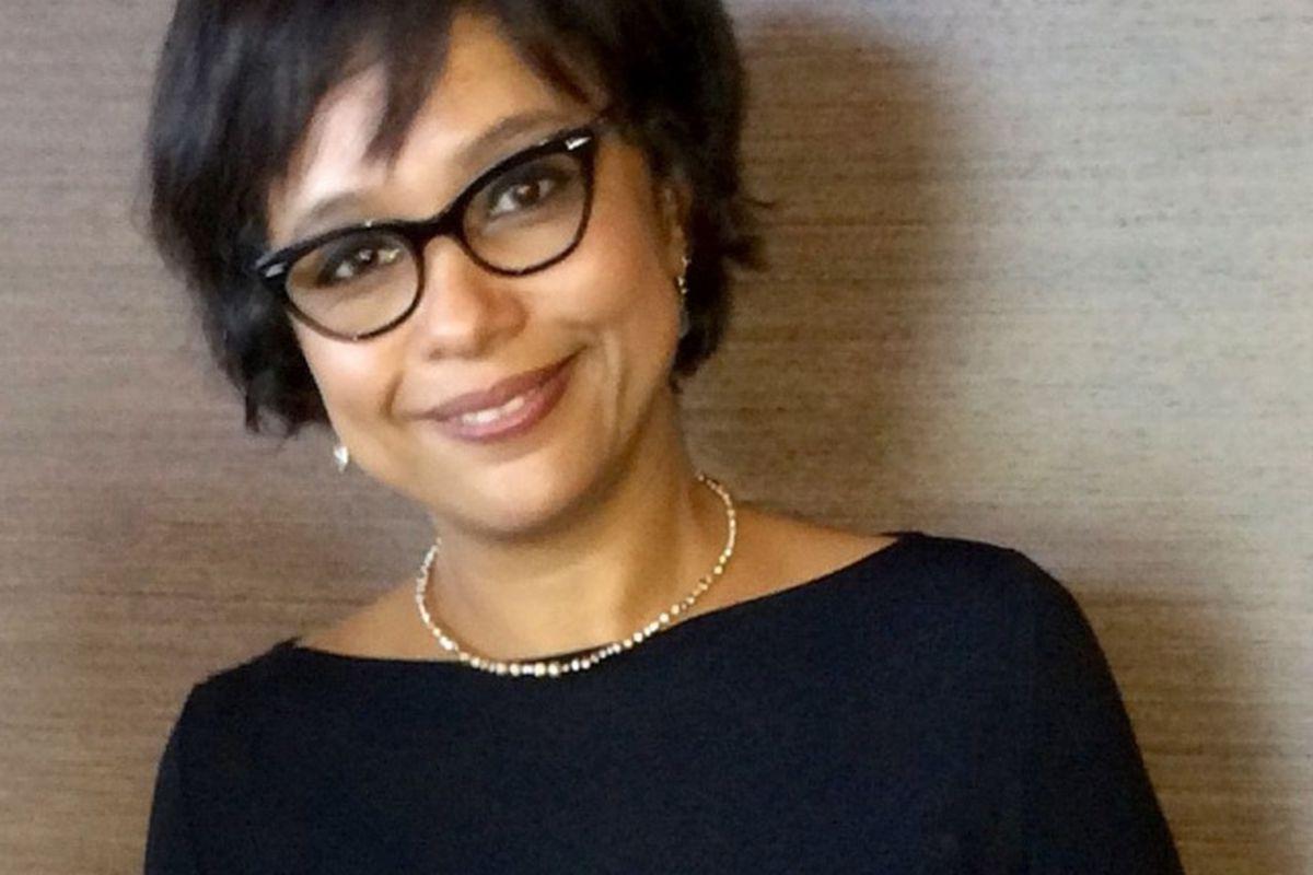 Woman with short, dark brown hair, black cat-eye glasses, black shirt, short necklace
