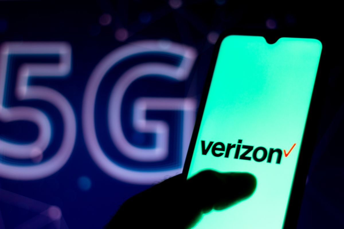 In this photo illustration the Verizon Communications logo seen displayed on a smartphone with the 5G inscription background.