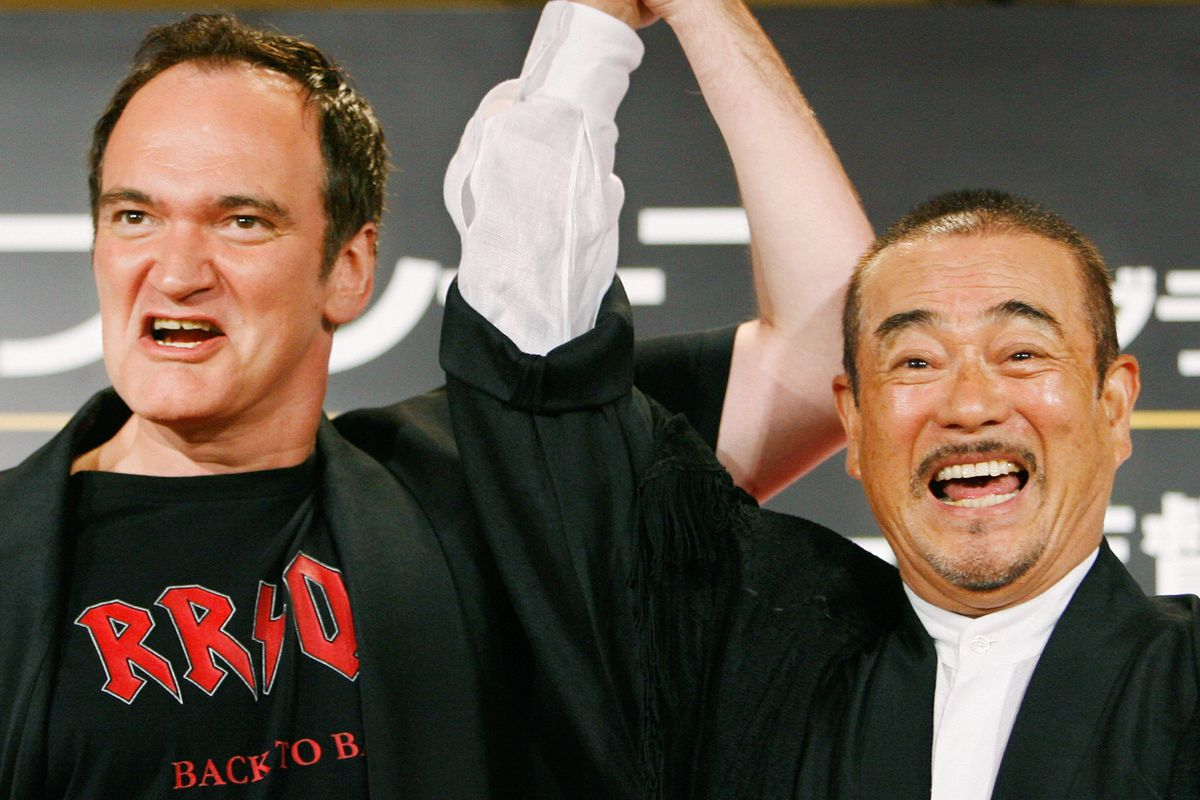 """Quentin Tarantino shares a light moment with Japanese actor Sonny Chiba during a press conference to promote his new film """"Death Proof"""" in Tokyo. August 2007."""