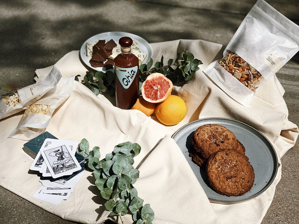 A picnic spread featuring a white blanket, some green leaves, cookies, a brown aperitif, and some cut up grapefruits
