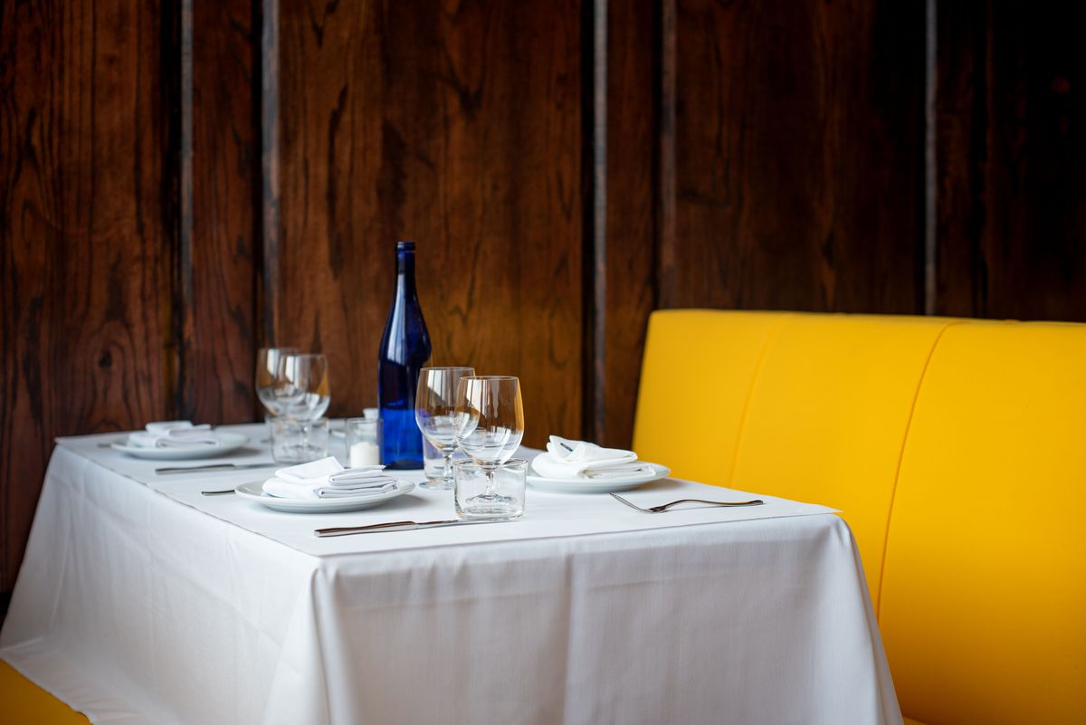 An off-center table set for dinner with a dark wooden background.