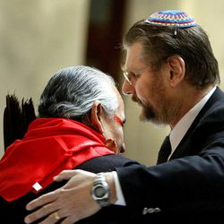 """Lacee Harris, a Native American shaman, and Alan Bachman of Chabad Lubavitch embrace during a """"blessing ceremony"""" to mark the first day of Interfaith Month at the Utah State Capitol in Salt Lake City on Friday, Feb.1, 2013."""