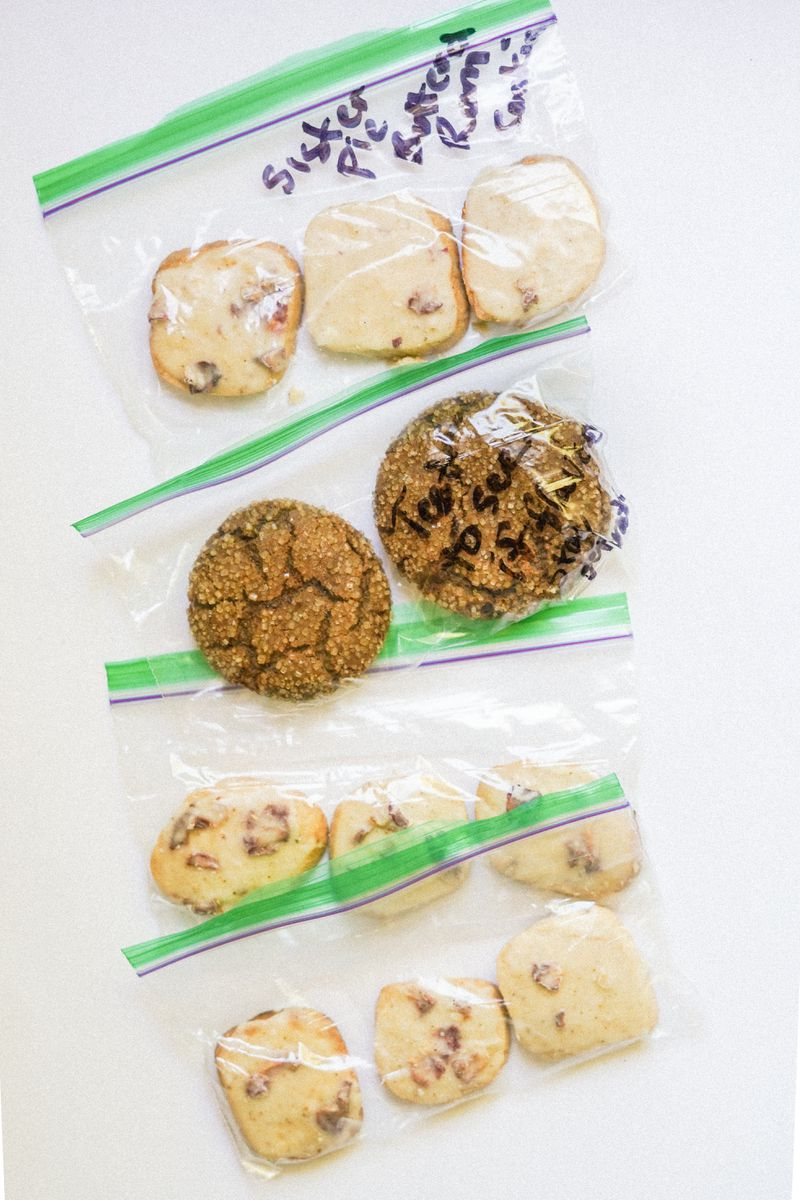Two different kinds of cookies, placed in groups of 2 or 3 in small zip-top plastic bags.