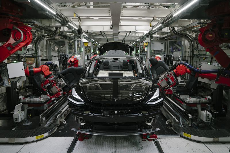 A Tesla automobile being built in a factory.