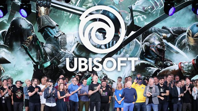 Ubisoft co-founder and CEO Yves Guillemot (blue sweater and pants, beneath the T in Ubisoft) closes the publisher's E3 2018 press briefing, flanked by developers and staff.