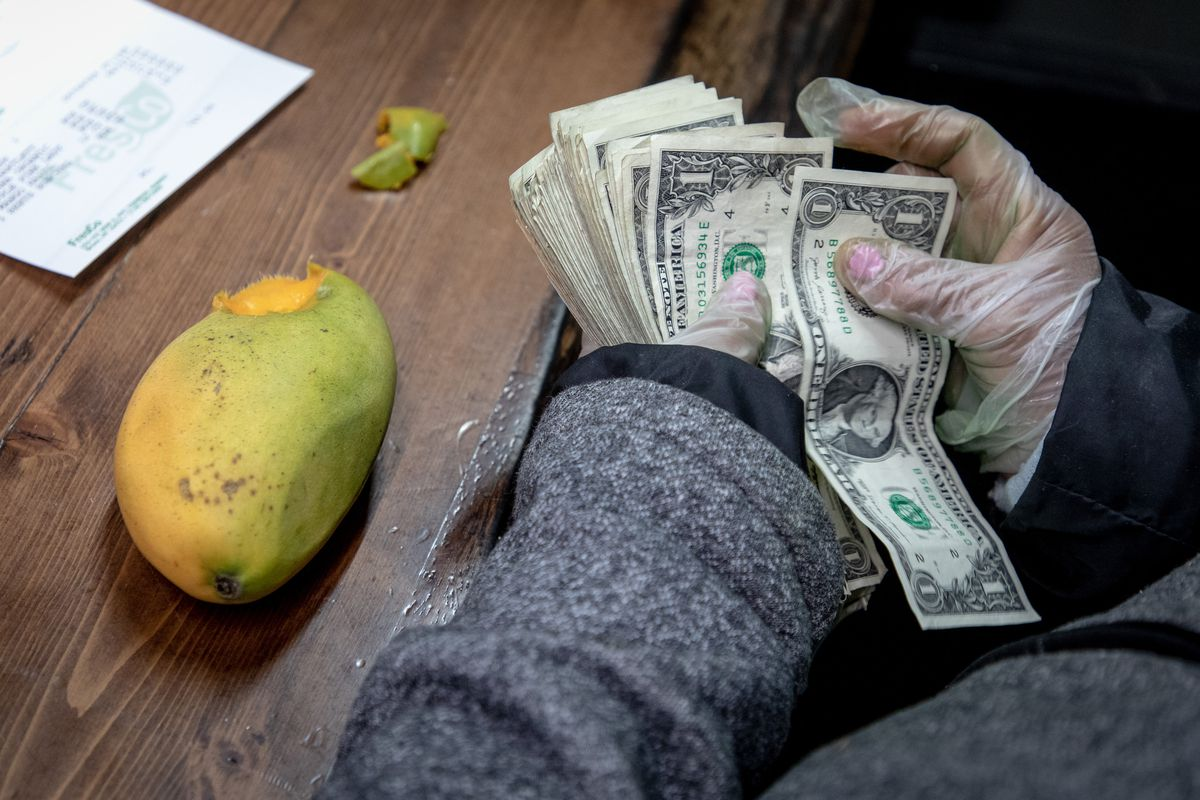 A street vendor counts out cash to pay for produce