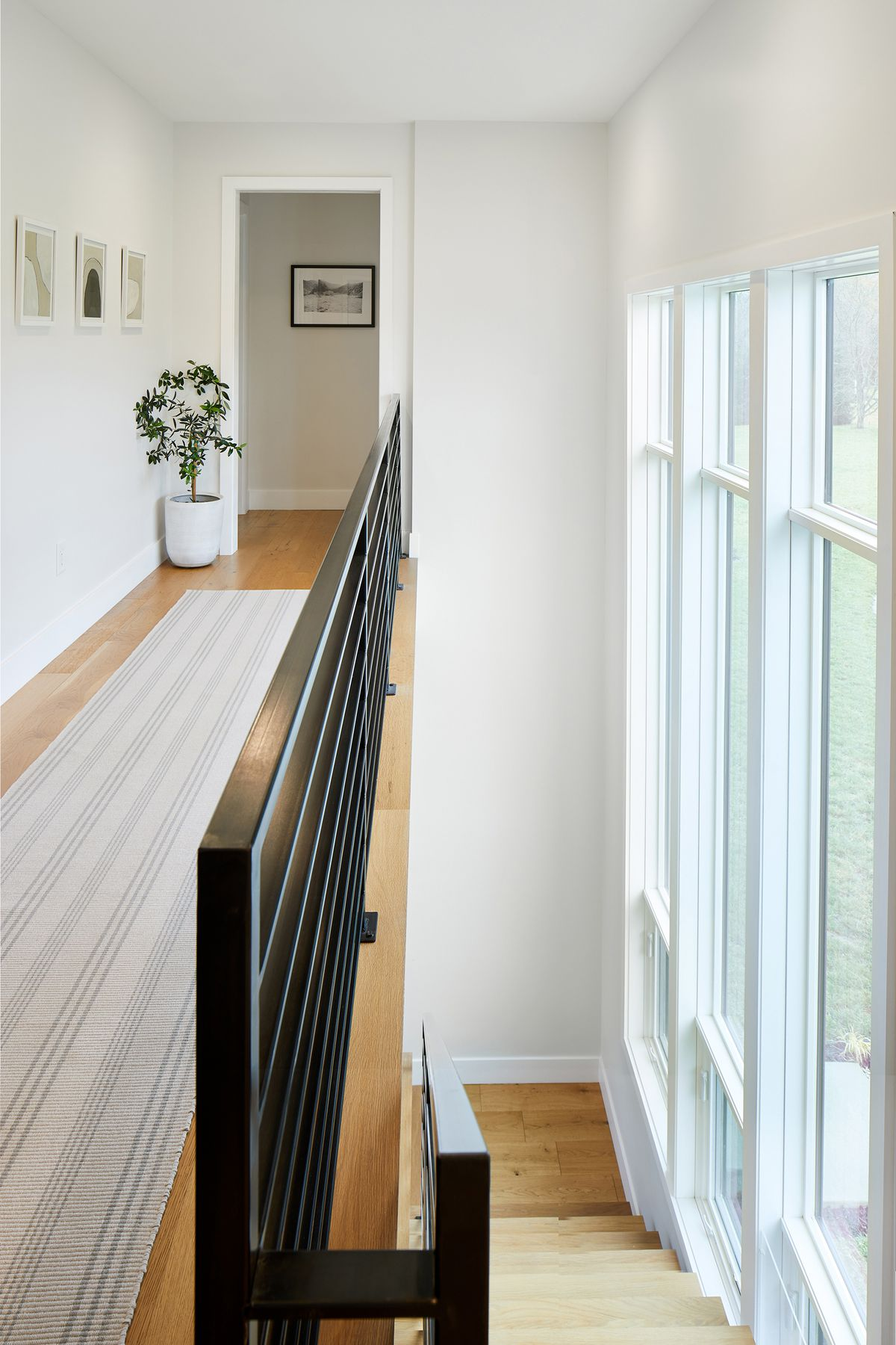 A hallway. The floor is hardwood and there is an area rug with a striped pattern. There are multiple framed works of art hanging on the wall which is painted white. The other wall has floor to ceiling windows that go up two stories high. The windowed wall