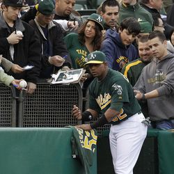 Oakland Athletics' Yoenis Cespedes (52) signs autographs for fans prior to the baseball game against the Kansas City Royals Monday, April 9, 2012, in Oakland, Calif.