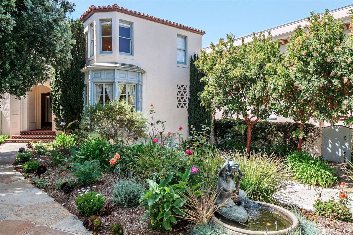 The garden and facade of 320 Seacliff, including a decorative fountain with statue.