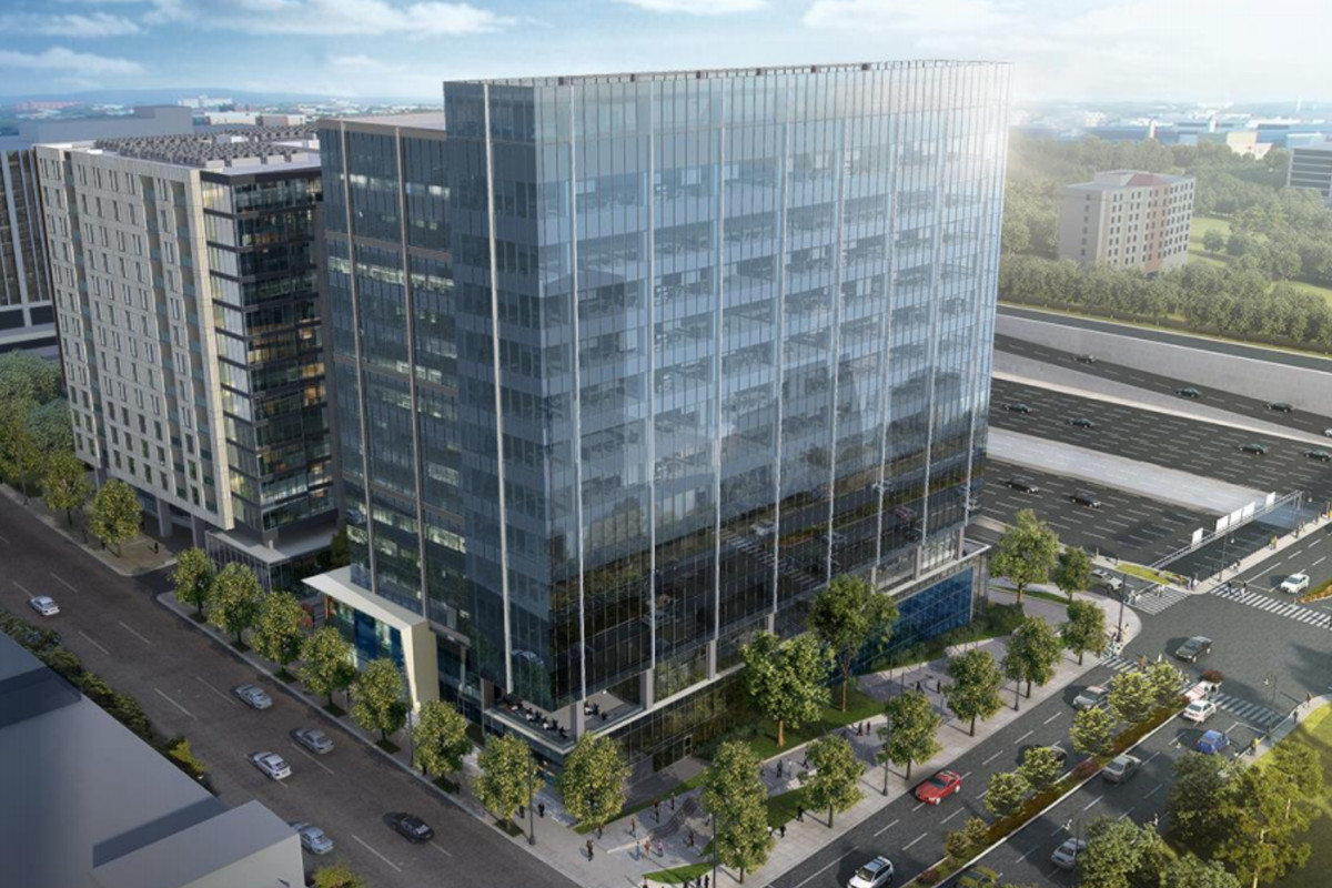 A sleek, glassy office building reflects sunlight and towers over sidewalks dotted with trees.