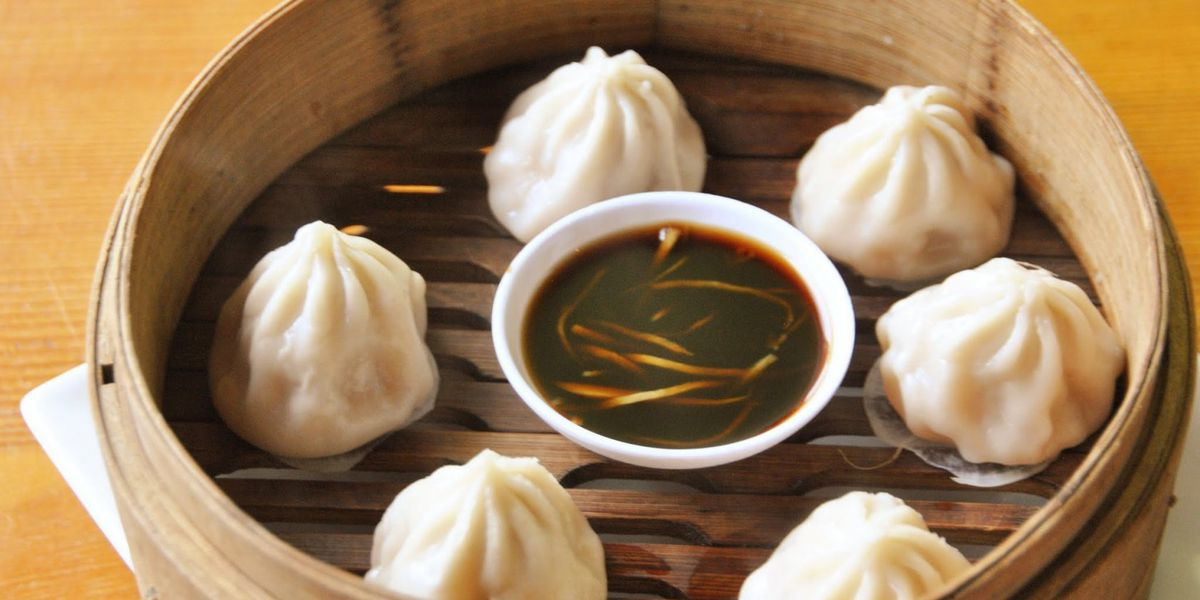 Six small steamed buns sit in a bamboo steamer basket, surrounding a small white bowl of black vinegar with slices of ginger