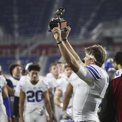 Brigham Young Cougars quarterback Zach Wilson holds up the MVP trophy after the Boca Raton Bowl in Boca Raton, Fla., on Tuesday, Dec. 22, 2020. BYU won 49-23.