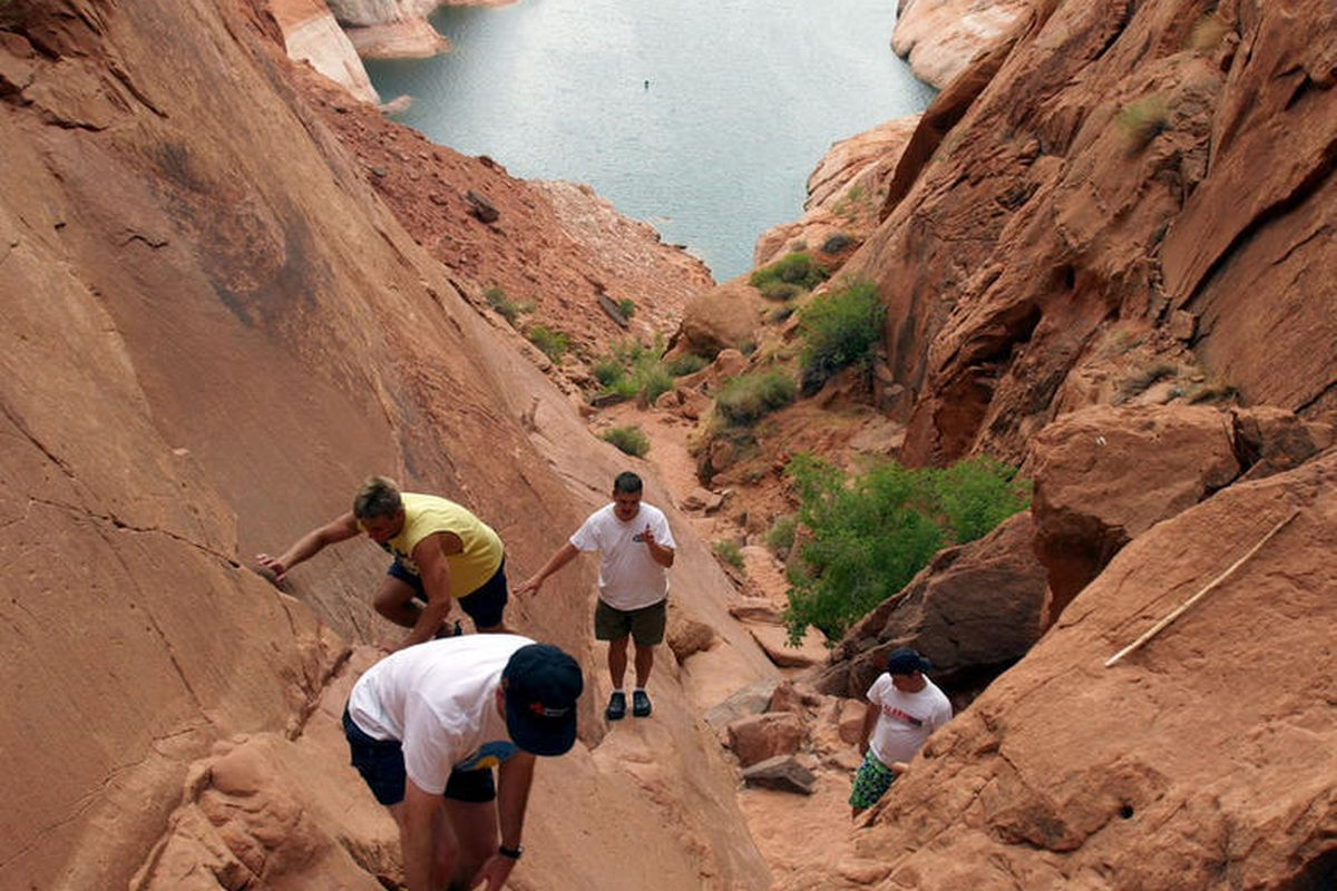 FILE - Hikers climb the Hole in the Rock at Lake Powell on Aug. 21, 2003.