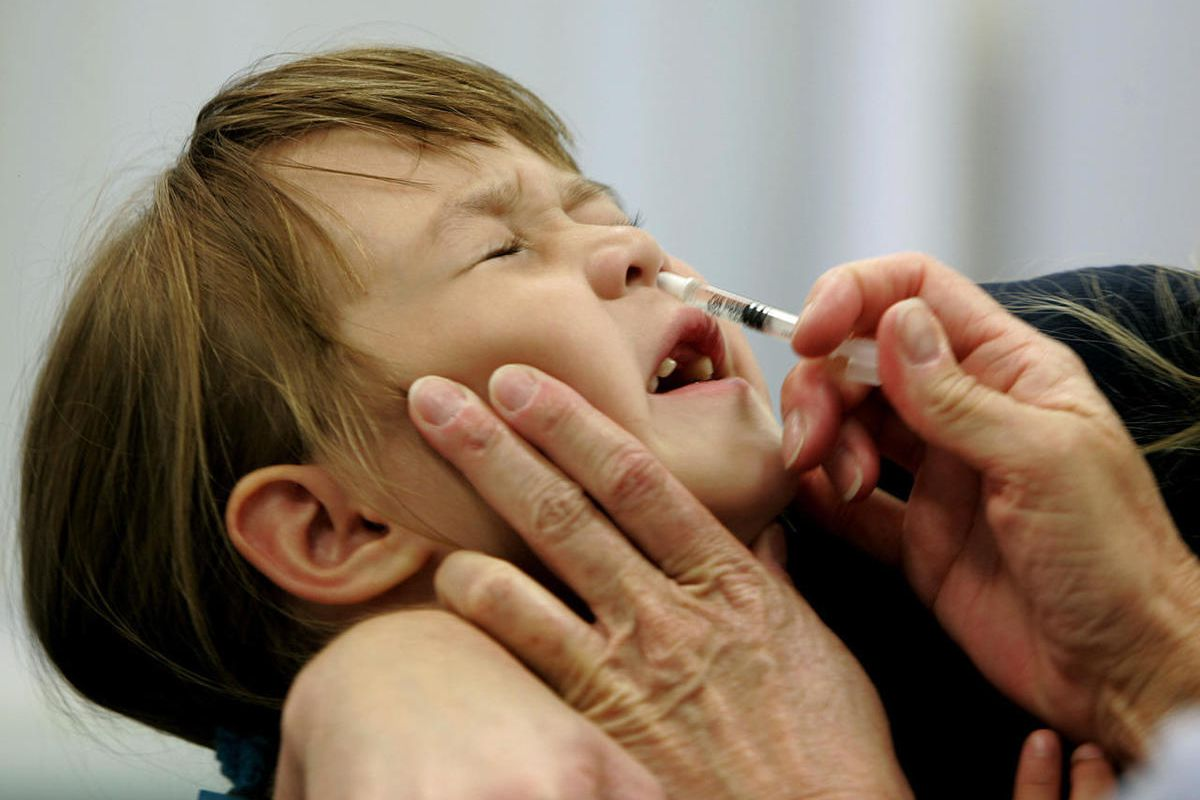 FILE- In this Oct. 4, 2005 file photo, a Danielle Holland reacts as she is given a FluMist influenza vaccination in St. Leonard, Md. On Wednesday, June 22, 2016, federal officials reported the latest in a growing series of study findings that show AstraZe
