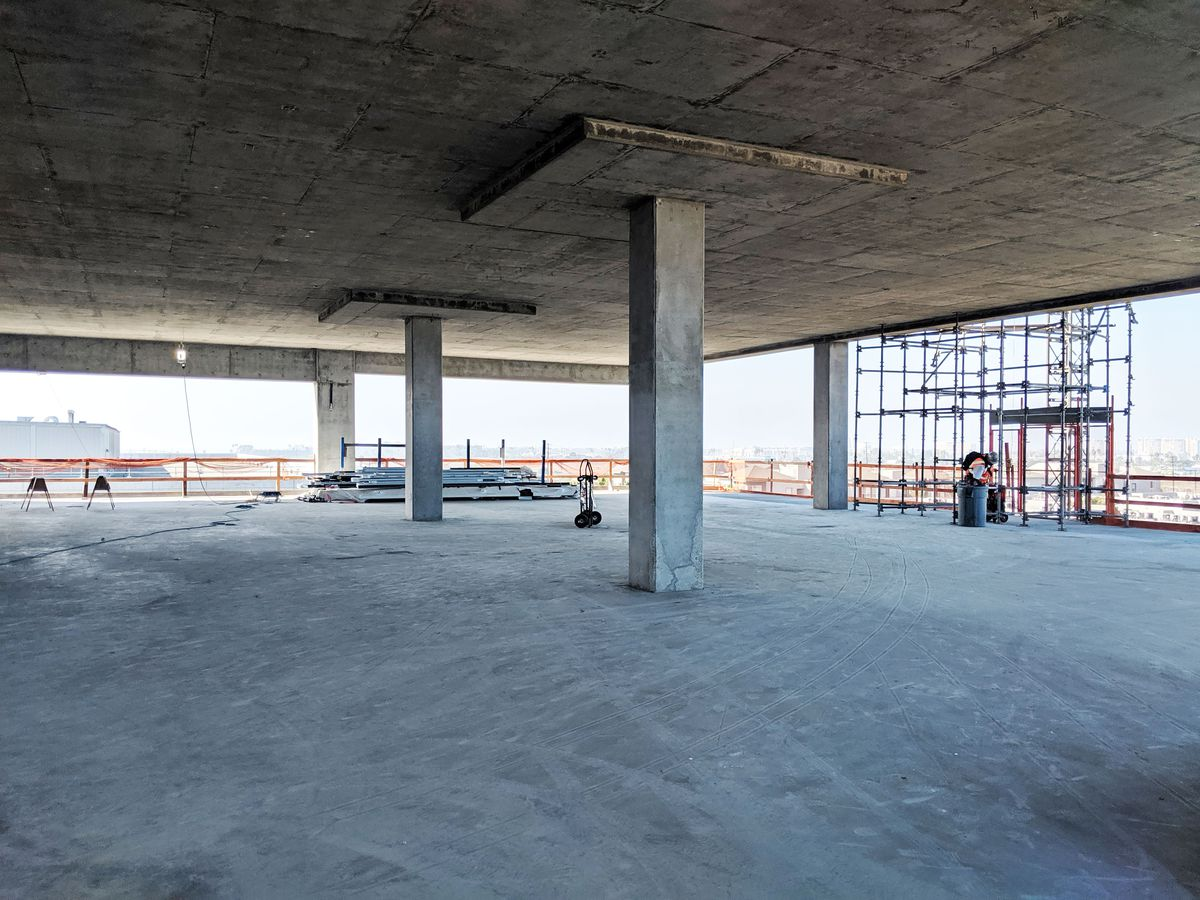 A photo of an incomplete office level, with no windows and just concrete floors and pillars visible.