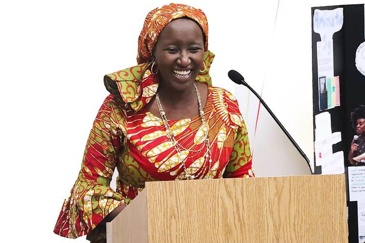Wearing a colorful dress and scarf, Amnata Sy speaks at a lectern