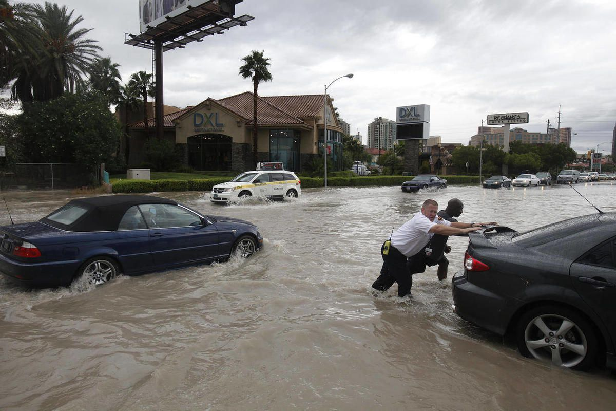 People push a stalled car off of a flooded street in Las Vegas Tuesday, Sept. 11, 2012. Intense thunderstorms drenched parts of the Southwest on Tuesday, delaying flights and stranding motorists in the Las Vegas area and flooding two mobile home parks in